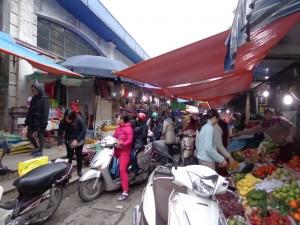 Dans le marché du quartier, les allées sont étroites, mais les scooters s'engagent quand même !
